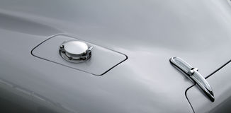 Classic sports car gas cap and trunk. 1950s british classic sports car gas cap and trunk lid and chromed hinge detail Stock Photos