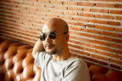30-40s brody portreta mężczyzny łysy obsiadanie na kanapie z czerwonego brązu wewnętrznej ściany ceglanym tłem zdjęcia stock