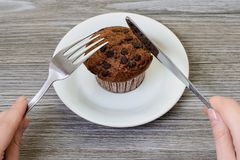 It`s brunch time! Woman`s hands trying to cut tasty fresh appeti. Sing chocolate muffin on white plate. Close up photo Stock Image