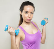 20s brunette girl exercising with dumb bells for toned arms and wellness Stock Photo