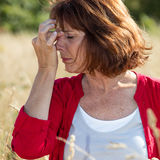 50s brunette woman massaging nose to soothe sinus pain outdoors. Hay fever allergies - beautiful aging woman with sinus pain massaging her nose against headache Royalty Free Stock Photography