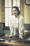 1950s business woman leaning on desk Stock Image