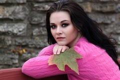 20's caucasian brunette holding big maple leaf Royalty Free Stock Photo