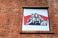 A 1960s Chinese poster on the red brick . Royalty Free Stock Images