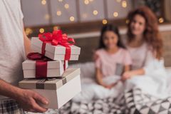 It`s Christmas time. ! Cute little girl and her beautiful mom are lying in bed, dad is holding presents in the foreground Royalty Free Stock Photo