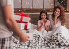 It`s Christmas time. ! Cute little girl and her beautiful mom are lying in bed and smiling while their dad is holding presents Stock Photos