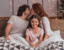 It`s Christmas time. ! Cute little girl and her parents are smiling while lying in bed at home, parents are kissing Stock Photo