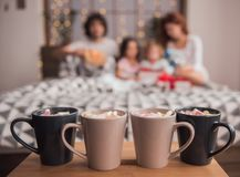 It`s Christmas time. ! Four cup of hot cocoa with marshmallow on the table, family in bed in the background Royalty Free Stock Images
