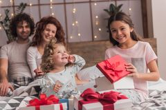 It`s Christmas time. ! Happy family sitting in bed, parents are smiling while their daughters are opening the presents Royalty Free Stock Photo