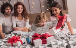 It`s Christmas time. ! Happy family sitting in bed, parents are smiling while their daughters are opening the presents Royalty Free Stock Image