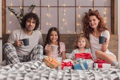 It`s Christmas time. ! Happy parents and their daughters are holding cups and smiling while sitting on bed with presents Royalty Free Stock Photo