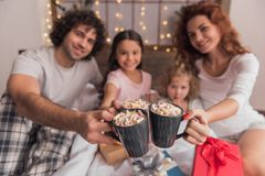 It`s Christmas time. ! Happy parents and their daughters are holding cups and smiling while sitting on bed with presents Stock Photos