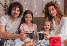 It`s Christmas time. ! Happy parents and their daughters are holding cups and smiling while sitting on bed with presents Stock Images