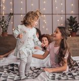 It`s Christmas time. ! Happy parents and their daughters are opening the presents and smiling while spending time together in bed at home Royalty Free Stock Photography