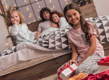 It`s Christmas time. ! Happy parents and their daughters are opening the presents and smiling while spending time together in bed at home Stock Photos
