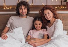 It`s Christmas time. ! Cute little girl and her parents are looking at camera and smiling while lying in bed at home Stock Photography