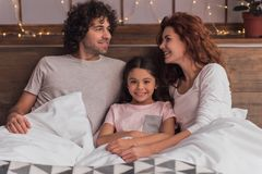 It`s Christmas time. ! Cute little girl and her parents are smiling while lying in bed at home Stock Photos