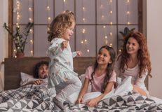 It`s Christmas time. ! Cute little girls are playing and smiling while spending time together with their parents in bed at home Stock Images