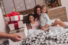 It`s Christmas time. ! Cute little girls and their beautiful mom are lying in bed and smiling while dad is holding presents Royalty Free Stock Photos