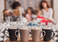 It`s Christmas time. ! Four cup of hot cocoa with marshmallow on the table, family in bed in the background Royalty Free Stock Photos