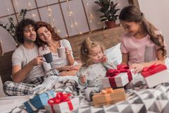 It`s Christmas time. ! Happy family sitting in bed, parents are drinking hot cocoa while their daughters are opening the presents Stock Images