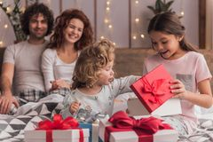 It`s Christmas time. ! Happy family sitting in bed, parents are smiling while their daughters are opening the presents Stock Photos
