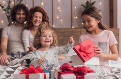 It`s Christmas time. ! Happy family sitting in bed, parents are smiling while their daughters are opening the presents Royalty Free Stock Photography