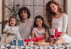 It`s Christmas time. ! Happy parents and their daughters are opening the presents, looking at camera and smiling while sitting in bed at home Royalty Free Stock Images