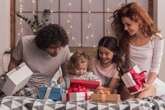 It`s Christmas time. ! Happy parents and their daughters are opening the presents and smiling while sitting in bed at home Stock Photo