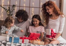 It`s Christmas time. ! Happy parents and their daughters are opening the presents and smiling while sitting in bed at home Royalty Free Stock Image