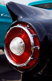 1950's Classic Car Fin & Taillight. The atomic age fin and tail light of a classic 1950's car at a car show with a classic truck in the background royalty free stock photography