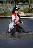 That's Cold. Cowgirl crossing pond on grey horse gets wet stock photo