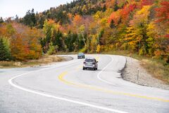 Mountain pass road lined with colourful deciduous trees at the peak of fall foliage