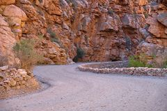 Gravel road of the Karoo. S curve gravel road carved into orange colored rocky canyon stock image