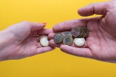 ` S d'hommes et paumes du ` s de femmes avec des pièces de monnaie L'homme passe les pièces de monnaie à la femme Manque d'argent Photos stock