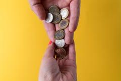 ` S d'hommes et paumes du ` s de femmes avec des pièces de monnaie L'homme passe les pièces de monnaie à la femme Manque d'argent Photos libres de droits