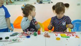 ` S das crianças que desenvolve uma sala de jogo Emoções das jovens crianças durante classes divertidos as crianças pintam com de video estoque
