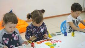 ` S das crianças que desenvolve uma sala de jogo Emoções das jovens crianças durante classes divertidos as crianças pintam com de filme