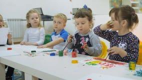` S das crianças que desenvolve uma sala de jogo Emoções das jovens crianças durante classes divertidos as crianças pintam com de vídeos de arquivo