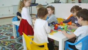 ` S das crianças que desenvolve uma sala de jogo Emoções das jovens crianças durante classes divertidos Construções da construção video estoque