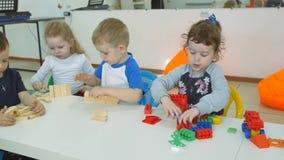 ` S das crianças que desenvolve uma sala de jogo Emoções das jovens crianças durante classes divertidos Construções da construção filme
