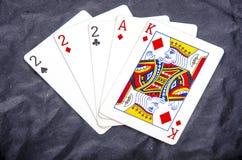 ` S de cinco naipes una mano de tres de un ` s de la clase dos y un as y un rey foto de archivo libre de regalías
