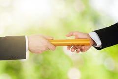 ` S de dos hombres de negocios que pasa un bastón de oro de la retransmisión imágenes de archivo libres de regalías