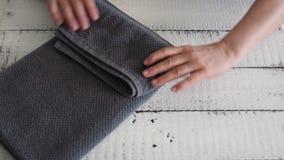 ` S de femme pliant une serviette grise pour la placer sur l'étagère banque de vidéos