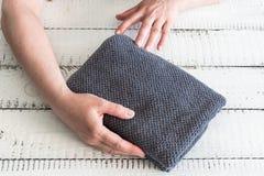 ` S de femme pliant une serviette grise pour la placer sur l'étagère Station thermale et bien-être, textile de Terry de coton photo stock