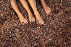 ` S de femmes et pieds du ` s d'hommes dans le sable Photographie stock