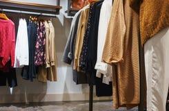 ` S de femmes et vêtements, robes et chemises sur des cintres et étagères dans un magasin d'habillement moderne image stock