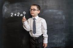 ` S de jeune garçon résolvant l'expression du ` s de maths De nouveau au concept d'école Réalité augmentée Garçon préscolaire fut Photographie stock