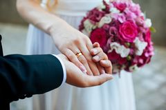 ` S de las mujeres y manos del ` s de los hombres con los anillos de bodas imagenes de archivo