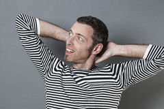 40s de relaxamento equipam o dobramento de seus braços atrás de seu pescoço Imagens de Stock